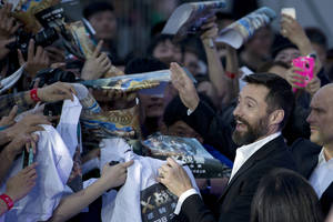 "Photo - Australian actor Hugh Jackman signs autographs for fans during the red carpet for his latest movie ""X-Men:Days of Future Past"" in Beijing, China, Tuesday, May 13, 2014. Jackman said Tuesday he wasn't ready to give up his 14-year role as the X-Men character Wolverine as he visited China to promote the franchise's latest movie, which has local elements intended to appeal to the massive Chinese audience. (AP Photo/Ng Han Guan)"