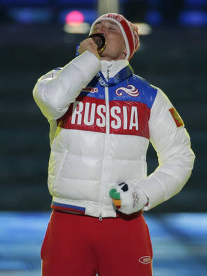 Photo - Russia's gold medal winner Alexander Legkov kisses his medal during the medals ceremony for the men's 50-kilometer cross-country race during the closing ceremony of the 2014 Winter Olympics, Sunday, Feb. 23, 2014, in Sochi, Russia. (AP Photo/Charlie Riedel)