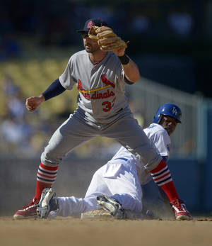 Photo -   Los Angeles Dodgers' Dee Gordon, bottom, looks back after being tagged out by St. Louis Cardinals second baseman Daniel Descalso while trying to steal second during the seventh inning of their baseball game on Sunday, Sept. 16, 2012, in Los Angeles. (AP Photo/Mark J. Terrill)
