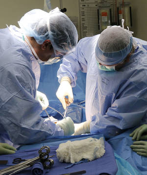 Photo - Surgeons perform a large bowel resection surgery at the OU Medical Center in Oklahoma City, OK, Tuesday, September 24, 2013,  Photo by Paul Hellstern, The Oklahoman