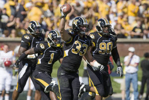 Photo - Missouri linebacker Luke Lambert, center, holds up the ball in the air after he recovered an Iowa State fumble during the first half of an NCAA college football game Saturday, Oct. 15, 2011, in Columbia, Mo. (AP Photo/L.G. Patterson) ORG XMIT: MOLG104
