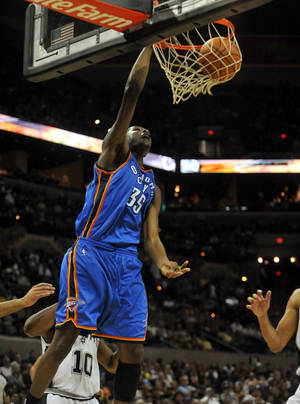 Photo - Oklahoma City's Kevin Durant dunks the ball against the San Antonio Spurs during the Thunder's 101-98 win Saturday. AP PHOTO
