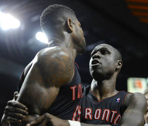 Photo - Toronto Raptors'  Mickael Pietrus, right, calms teammate Amir Johnson after he was ejected during the third quarter of an NBA  basketball game against the Portland Trail Blazers in Portland, Ore., Monday, Dec. 10, 2012. The Trail Blazers beat the Raptors 92-74. (AP Photo/Greg Wahl-Stephens)
