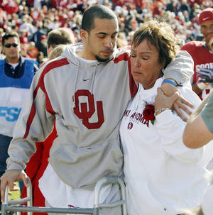 photo - OU's Corey Wilson, left, stands with his mother, Wendy Wilson, before the Bedlam college football game between the University of Oklahoma Sooners (OU) and the Oklahoma State University Cowboys (OSU) at the Gaylord Family --Oklahoma Memorial Stadium on Saturday, Nov. 28, 2009, in Norman, Okla. Before the game Corey Wilson walked on Owen Field for the first time at a game since a car wreck left him partially paralyzed in February.   Photo by Nate Billings, The Oklahoman