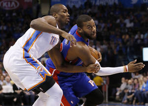 Photo - Detroit Pistons forward Greg Monroe drives around Oklahoma City Thunder forward Serge Ibaka during the first quarter of an NBA basketball game in Oklahoma City, Wednesday, April 16, 2014. (AP Photo/Sue Ogrocki)