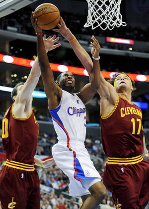 Photo -   Los Angeles Clippers guard Chris Paul, center, drives between Cleveland Cavaliers forward Tyler Zeller, left, and center Anderson Varejao (17) in the first half of an NBA basketball game, Monday, Nov. 5, 2012, in Los Angeles. (AP Photo/Gus Ruelas)