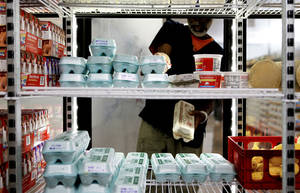 Photo - John Henry Martin looks at produce and dairy products at the City Rescue Mission's new Impact Hunger Food Resource Center, 831 W California, on Wednesday. Photo by BRYAN TERRY, THE OKLAHOMAN