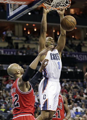 Photo - Charlotte Bobcats' Gerald Henderson (9) dunks on Chicago Bulls' Taj Gibson during the first half of an NBA basketball game in Charlotte, N.C., Saturday, Jan. 25, 2014. (AP Photo/Chuck Burton)
