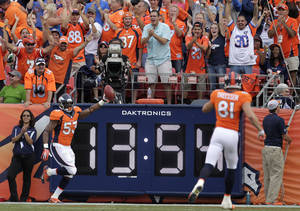 Photo - Denver Broncos linebacker Steven Johnson (53) celebrates after picking up a blocked punt and running it back for a touchdown against the Philadelphia Eagles in the fourth quarter of an NFL football game, Sunday, Sept. 29, 2013, in Denver. (AP Photo/Joe Mahoney)