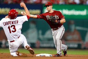 Photo - Arizona Diamondbacks shortstop Chris Owings, right, throws to first base for a double play after making an out against St. Louis Cardinals' Matt Carpenter during the third inning of a baseball game Wednesday, May 21, 2014, in St. Louis. Kolten Wong was out at first. (AP Photo/Scott Kane)