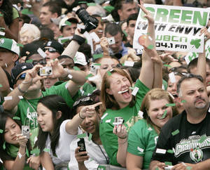 Photo - Celtics fans, who are known as some of the NBA's loudest and most educated fans, cheer the team as it passes by during the 2008 NBA Championship victory parade. AP photo