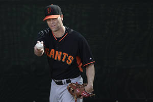 Photo - San Francisco Giants pitcher Tim Hudson warms up to throw during spring training baseball practice on Sunday, Feb. 16, 2014, in Scottsdale, Ariz. (AP Photo/Gregory Bull)
