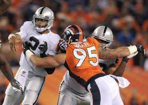 Photo - FILE - In this Sept. 23, 2013 file photo, Oakland Raiders quarterback Terrelle Pryor (2) is hit by Denver Broncos defensive end Derek Wolfe (95) after throwing a pass in the second quarter of an NFL football game, in Denver. Wolfe says he's finally healthy after suffering a seizure in November that doctors now believe was related to the spinal cord injury he suffered in the preseason. In an interview outside his home with Denver television stations KCNC and KMGH this week, the Broncos' defensive lineman said he's back up to 280 pounds, having regained 20 of the 30 pounds he lost last season, and was ready to return to training next week. (AP Photo/Jack Dempsey, File)