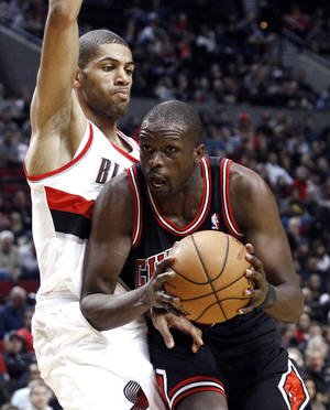 Photo -   Portland Trail Blazers forward Nicolas Batum, left, from France, plays tight defense on Chicago Bulls forward Luol Deng during the first quarter of their NBA basketball game in Portland, Ore., Sunday, Nov. 18, 2012. (AP Photo/Don Ryan)