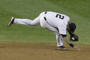 Photo -   New York Yankees shortstop Derek Jeter injures himself fielding a ball in the 12th inning of Game 1 of the American League championship series against the Detroit Tigers early Sunday, Oct. 14, 2012, in New York. (AP Photo/Kathy Willens)