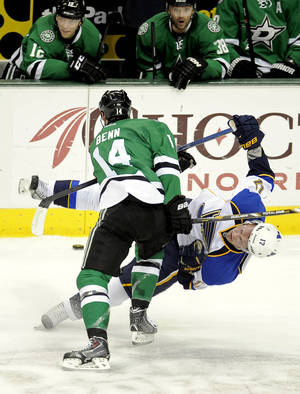 Photo - Dallas Stars left wing Jamie Benn (14) checks St. Louis Blues center Vladimir Sobotka (17) in front of the Stars bench during the first period of an NHL hockey game, Sunday, Dec. 29, 2013, in Dallas. (AP Photo/Matt Strasen)