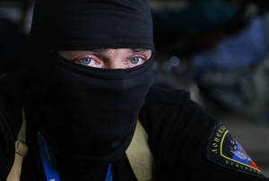 Photo - A masked pro-Russian activist guard looks through a window of the regional administration building seized earlier in Donetsk, Ukraine, Friday, April 18, 2014. Pro-Russian insurgents in Ukraine's east who have been occupying government buildings in more than 10 cities said Friday they will only leave them if the interim government in Kiev resigns.(AP Photo/Sergei Grits)