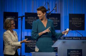 Photo - South African Academy Award-winning actress Charlize Theron, right, gestures as she  accepts her Crystal award from Hilde Schwab on the eve of the opening of the 43rd Annual Meeting of the World Economic Forum, WEF, in Davos, Switzerland, Tuesday, Jan. 22, 2013.  (AP Photo/Anja Niedringhaus)