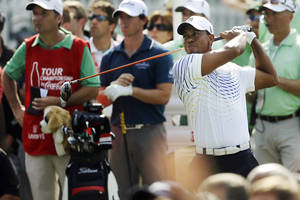Photo -   Tiger Woods hits from the tee on the 13th hole during the first round of the Tour Championship golf tournament, Thursday, Sept. 20, 2012, in Atlanta. (AP Photo/John Bazemore)