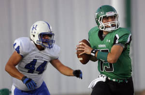 Photo - Jones' Michael Lowe looks to throw as Hennessey's Car Aguirre chases him down during the high school football game between Jones and Hennessey  Friday, Sept. 9, 2011. Photo by Sarah Phipps, The Oklahoman