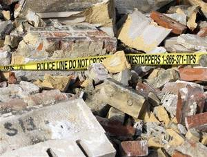 Photo - Rubble from the upper portions of a 1920s-era building is strewn about the sidewalk in St. Louis. Pre-dawn strong winds were blamed for the partial building collapse that sent bricks, mortar, roofing and some window air conditioning units raining down onto a sidewalk. (AP Photo/Tom Gannam