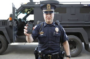 Photo - In a May 6, 2014 photo, Sgt. Andres Wells of the Kalamazoo Dept. of Public Safety, who successfully used text messaging to negotiate with a suicidal robbery suspect during a 2011 standoff, stands next to his armored vehicle. With 6 billion text messages exchanged daily in the United States, texting is becoming a more frequent part of police crisis negotiations. (AP Photo/Mark Bugnaski)