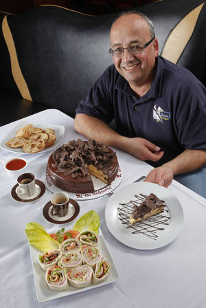 Photo - Rudy Khouri, pastry chef at La Baguette, shows a slice of Boston Cream Pie in Norman <strong>STEVE SISNEY - THE OKLAHOMAN</strong>
