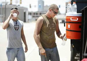 Photo - Kyle Kersten (left) and Jesse Smith, with Centennial Landscaping, take a water break while working on the landscaped right-of-ways in downtown Oklahoma City, OK, Thursday, July 28, 2011. <strong>The Oklahoman - Paul Hellstern</strong>