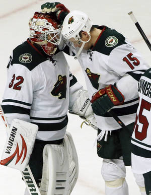 Photo - Minnesota Wild goalie Niklas Backstrom (32) celebrates with Dany Heatley (15) after the Wild defeated the Chicago Blackhawks 5-3 in an NHL hockey game in Chicago, Saturday, Oct. 26, 2013. (AP Photo/Nam Y. Huh)