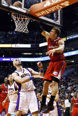 Photo - Los Angeles Clippers' Blake Griffin, right, misses a dunk in front of Phoenix Suns' Marcin Gortat, of Poland, during the first half in an NBA basketball game, Thursday, Jan. 24, 2013, in Phoenix. (AP Photo/Ross D. Franklin)