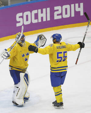 Photo - Sweden goaltender Henrik Lundqvist and Sweden defenseman Niklas Kronwall celebrate their team's 2-1 victory over Finland in the men's semifinal ice hockey game at the 2014 Winter Olympics, Friday, Feb. 21, 2014, in Sochi, Russia. (AP Photo/Matt Slocum)