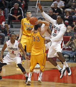 photo -   Wyoming guard Francisco Cruz gets caught between San Diego State defenders Jamaal Franklin, right, and Xavier Thames during the first half of an NCAA college basketball game Wednesday, Feb. 22, 2012, in San Diego. (AP Photo/Lenny Ignelzi )