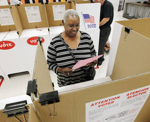 Photo -                    Mary Wilson, of Oklahoma City, reads a ballot Thursday during early voting for the June 24 primary at the Oklahoma County Election Board in Oklahoma City.                     Photo by Paul B. Southerland, The Oklahoman