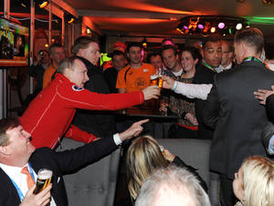 Photo - In this Sunday, Feb. 9, 2014 photo Russian President Vladimir Putin, background left, toasts with beer with people as King Willem-Alexander of the Netherlands, foreground left, and Queen Maxima, foreground center, look on at the Netherlands house in Sochi, during the 2014 Winter Olympics. (AP Photo/RIA Novosti Kremlin, Mikhail Klimentyev, Presidential Press Service)
