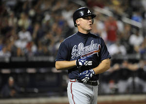 Photo -   Atlanta Braves' Chipper Jones takes his batting gloves off after he lined out for the third out during the fifth inning of a baseball game on Friday, Sept. 7, 2012, at Citi Field in New York. (AP Photo/Kathy Kmonicek)