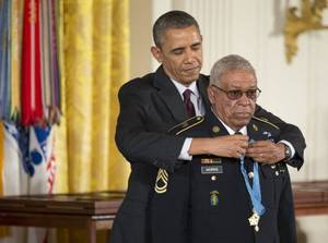 Photo - President Barack Obama awards Okmulgee native Army Staff Sgt. Melvin Morris the Medal of Honor during a ceremony in the East Room of the White House in Washington on Tuesday. President Obama awarded the Medals of Honor to 24 ethnic or minority U.S. soldiers who performed acts of bravery under fire in three of the nationís wars, that were denied because of prejudice. (AP Photo/Manuel Balce Ceneta)