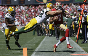 Photo - San Francisco 49ers quarterback Colin Kaepernick (7) runs out of bounds as Green Bay Packers outside linebacker Clay Matthews dives for him during the second quarter of an NFL football game in San Francisco, Sunday, Sept. 8, 2013. (AP Photo/Ben Margot)