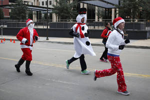 Photo - Runners approach the finish line during the SandRidge Santa Run in Oklahoma City, Saturday, Dec. 14, 2013.  Photo by Garett Ray Fisbeck, For The Oklahoman