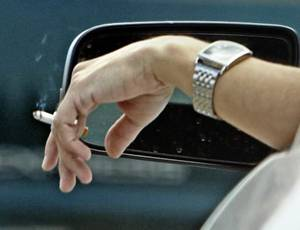Photo - A motorist holds a cigarette out of the window on State Highway 9 on Wednesday, April 6, 2011, in Norman, Okla. Photo by Steve Sisney, The Oklahoman