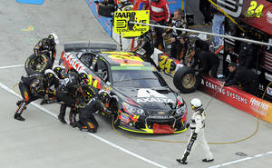Photo - Jeff Gordon make a pit stop during a NASCAR Sprint Cup Series auto race at Martinsville Speedway in Martinsville, Va., Sunday, March 30, 2014. (AP Photo/Mike McCarn)