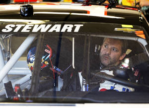 Photo - Driver Tony Stewart adjusts the rear view mirror in his car before going out on the track to practice for the NASCAR Sprint Unlimited auto race at Daytona International Speedway in Daytona Beach, Fla., Friday, Feb. 14, 2014.  Stewart has not raced in more than six months since he broke two bones in his leg in an August 2013 sprint-car crash.(AP Photo/John Raoux)