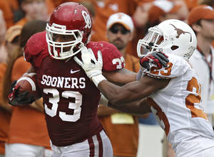 Photo - OU's Trey Millard (33) gets past UT's Carrington Byndom (23) during the Red River Rivalry college football game between the University of Oklahoma (OU) and the University of Texas (UT) at the Cotton Bowl in Dallas, Saturday, Oct. 13, 2012. Photo by Chris Landsberger, The Oklahoman