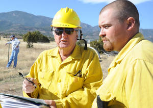 Photo -   Wetmore volunteer firemen Greg Tabuteau, left, and Dee Murphy discuss strategy for fighting a wildfire Thursday, Oct 24, 2012 in Wetmore, Colo. The fire started Wednesday afternoon near Tabuteau's home just west of Wetmoreand damaged at least 14 residences in the rural area. (AP Photo/Pueblo Chieftain, Chris McLean)