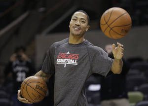 Photo - Chicago Bulls' Derrick Rose goes through pregame warmups before an NBA basketball game against the San Antonio Spurs, Wednesday, March 6, 2013, in San Antonio. (AP Photo/Eric Gay)