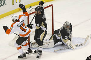 Photo - Philadelphia Flyers' Wayne Simmonds (17) celebrates past Pittsburgh Penguins' Rob Scuderi (4) after scoring on goalie Marc-Andre Fleury, right, during the first period of an NHL hockey game on Sunday, March 16, 2014, in Pittsburgh. (AP Photo/Keith Srakocic)