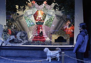 Photo - This Nov. 18, 2013 photo shows a woman walking her dog past a vintage Santa Claus holiday window display at Lord & Taylor department store in New York. Forget window shopping, some of Manhattan's biggest and most storied retailers say their elaborate seasonal window displays are a gift to passers-by.  (AP Photo/Mark Lennihan)