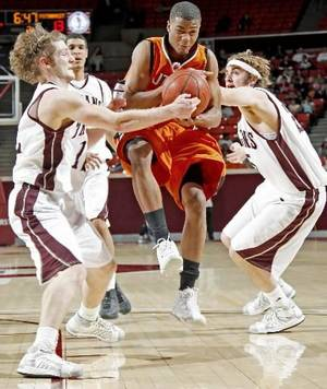 Photo - Putnam City's Tre Payne goes between  Jenks' Doug McKnight, left, and Brian Brookey during the Class 6A boy's championship game between Putnam City and  Jenks in the Oklahoma High School Basketball Championships at Lloyd Noble Arena in Norman, Okla., Saturday, March 14, 2009. PHOTO BY BRYAN TERRY, THE OKLAHOMAN