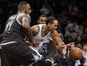 Photo - Orlando Magic forward Glen Davis (11) and Orlando Magic forward Maurice Harkless (21) defend Brooklyn Nets guard Shaun Livingston (14) in the first half of their NBA basketball game at the Barclays Center, Tuesday, Jan. 21, 2014 in New York. (AP Photo/Kathy Willens)