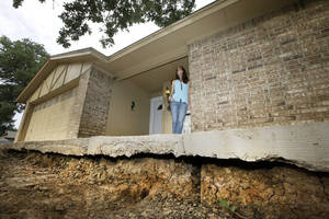 Photo - Barbara Brown poses for a photo on the front step of her home that now sits about one foot off the surface of her lawn, Saturday, June 21, 2014, in Reno, Texas. Brown said that the top of the step once sat about four inches off the surface of her lawn. Brown said she believes the sinkholes on her property and the drop of her lawn have to do with natural gas drilling. (AP Photo/Tony Gutierrez)