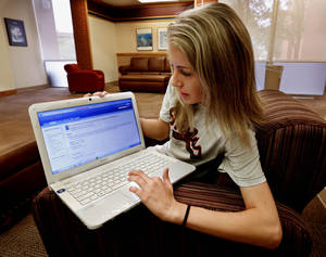 Photo - Freshman student Mandi Gatlin shows an e-textbook she used in a sociology class this year at the University of Oklahoma (OU) on Thursday, May 9, 2013 in Norman, Okla.  Photo by Steve Sisney, The Oklahoman